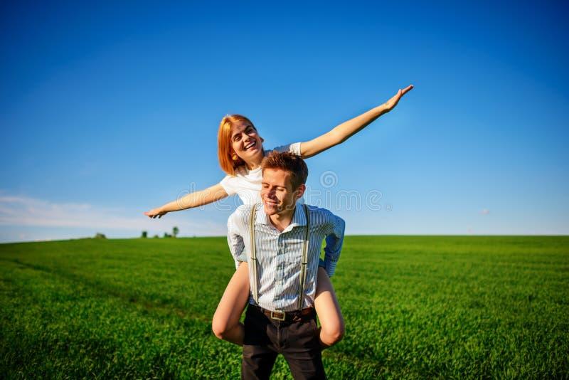 Uśmiechnięty mężczyzna trzyma dalej jego plecy szczęśliwa kobieta która ciągnie out go, obraz stock