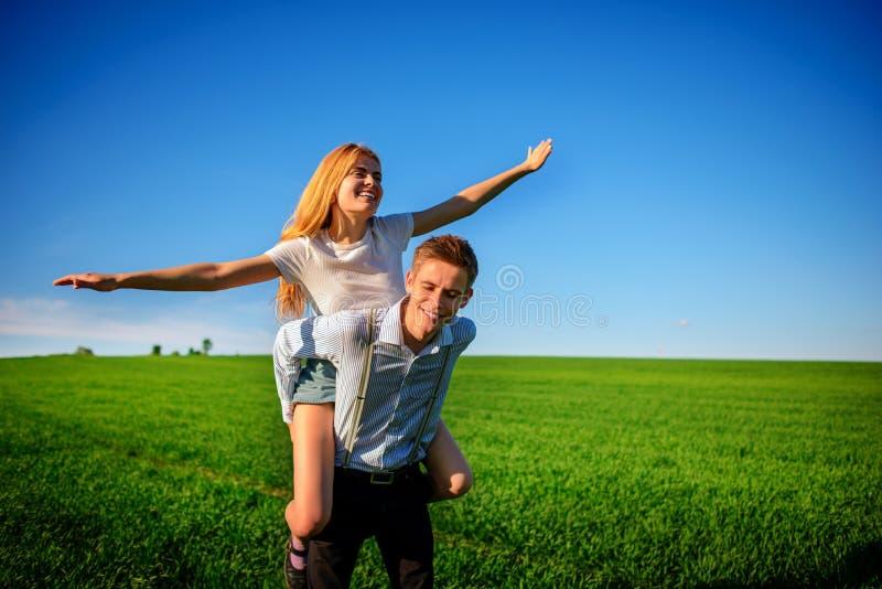 Uśmiechnięty mężczyzna trzyma dalej jego plecy szczęśliwa kobieta która ciągnie out go, fotografia stock