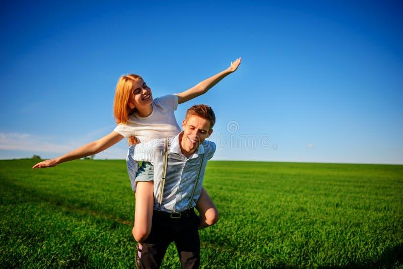 Uśmiechnięty mężczyzna trzyma dalej jego plecy szczęśliwa kobieta która ciągnie out go, zdjęcia stock