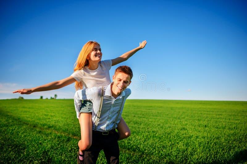 Uśmiechnięty mężczyzna trzyma dalej jego plecy szczęśliwa kobieta która ciągnie out go, obraz royalty free