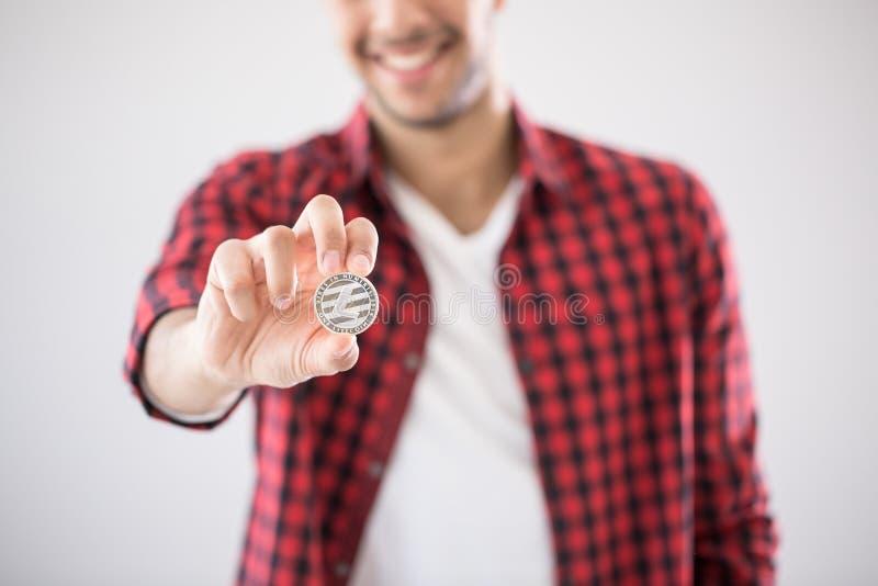 Uśmiechnięty mężczyzna trzyma srebną monetę litecoin - symbol wirtualny zdjęcia royalty free