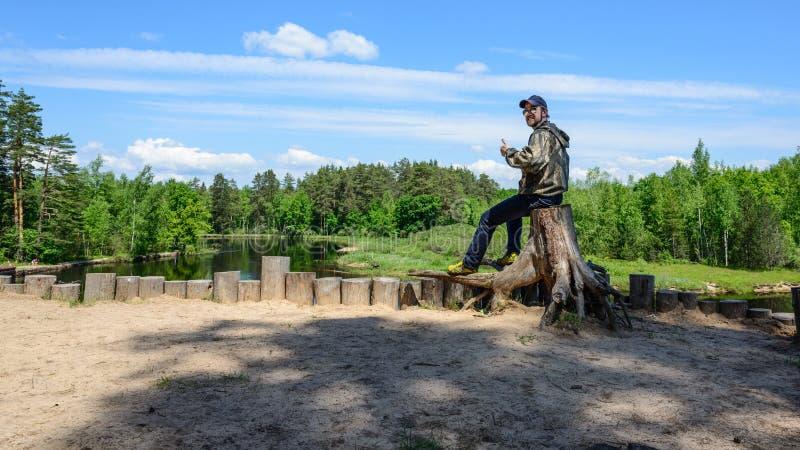 Uśmiechnięty mężczyzna turysta siedzi na drzewnym fiszorku zdjęcie stock