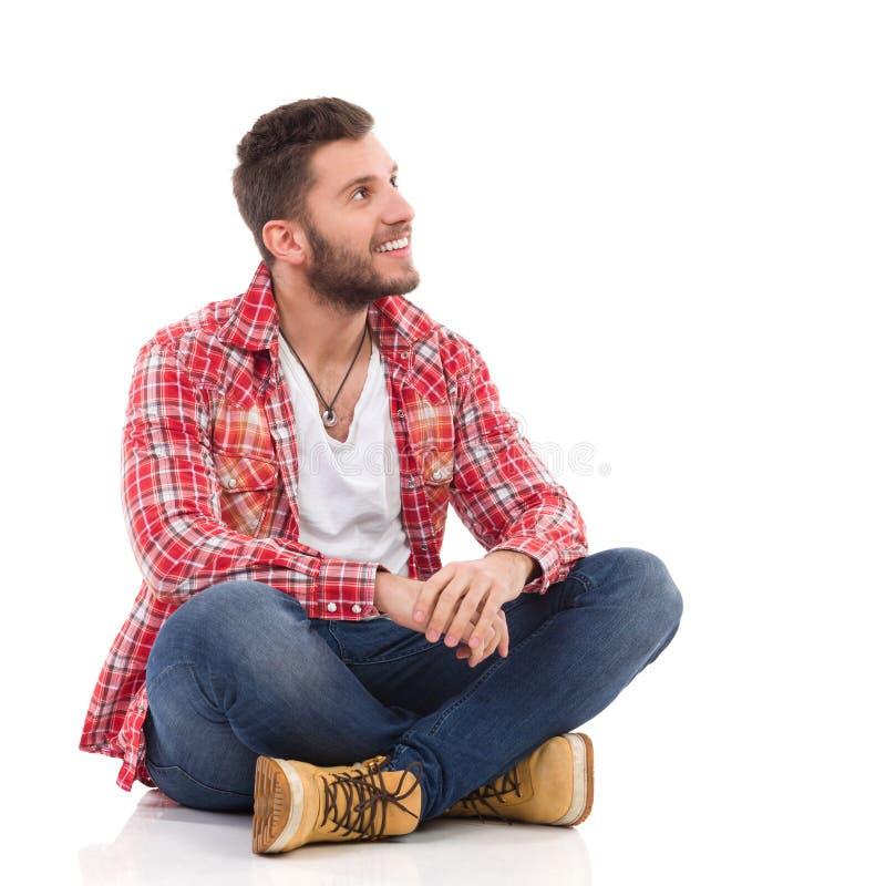 Uśmiechnięty mężczyzna w lumberjack koszulowym obsiadaniu z nogami krzyżować fotografia stock