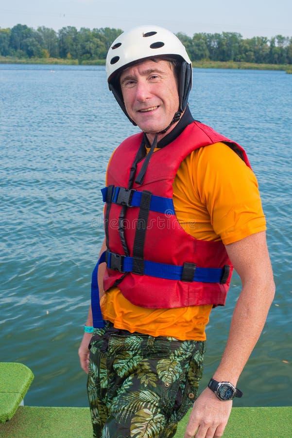 Uśmiechnięty mężczyzna, wakeboarder pozy dla kamery na tle o obraz royalty free