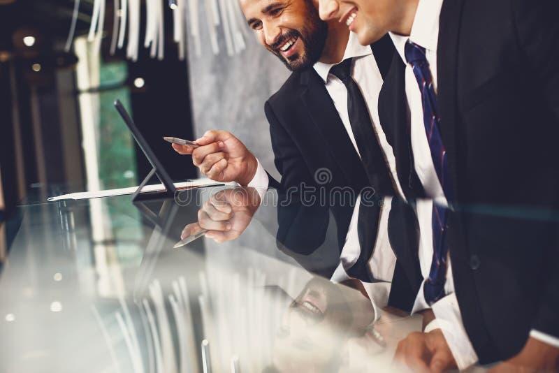 Uśmiechnięty mężczyzna wskazujący na ekran nowoczesnego tabletu podczas pracy z kolegą obrazy royalty free