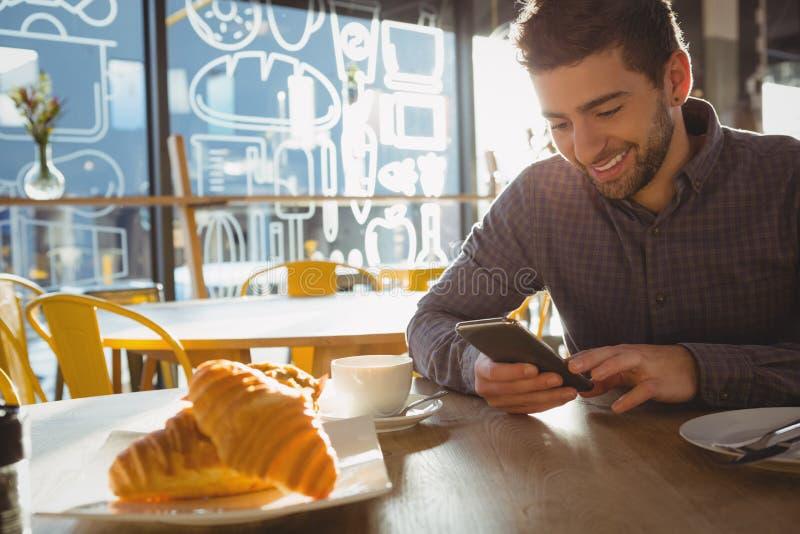 Uśmiechnięty mężczyzna z croissants używać telefon w kawiarni obraz stock