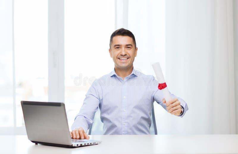 Uśmiechnięty mężczyzna z dyplomem i laptopem przy biurem obrazy royalty free