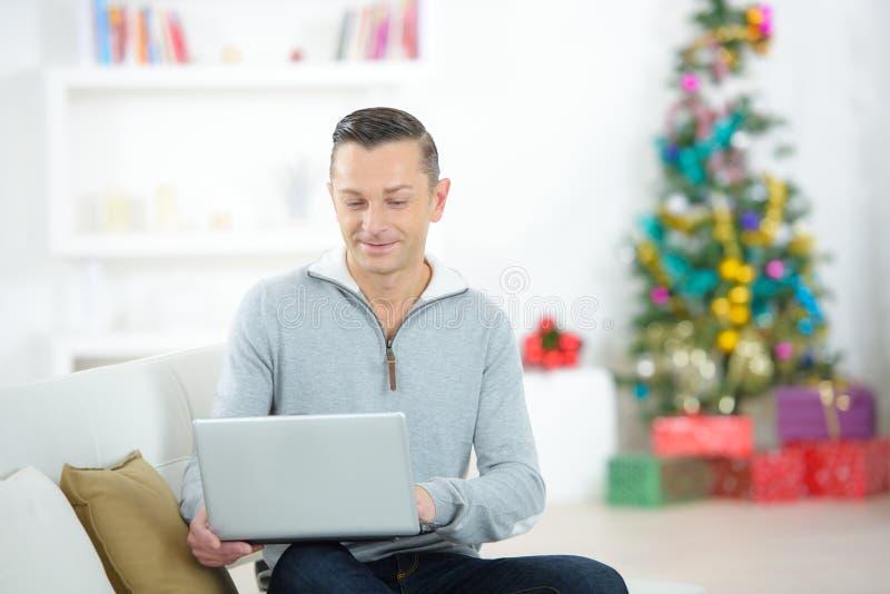 Uśmiechnięty mężczyzna z laptopu obsiadaniem na kanapie zdjęcie stock