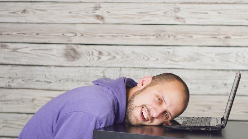 Uśmiechnięty mężczyzny obsiadanie w biurze i działaniu na laptopie zdjęcie royalty free