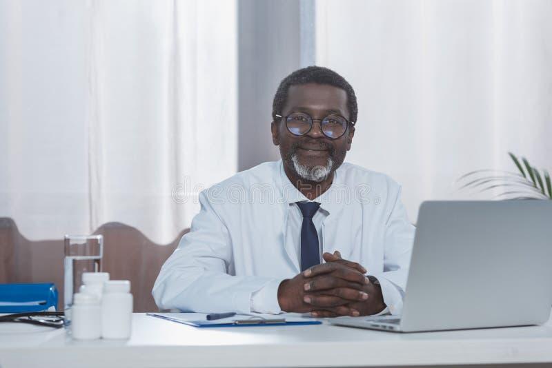 Uśmiechnięty męski amerykanin afrykańskiego pochodzenia lekarki obsiadanie przy patrzeć i stołem obraz royalty free
