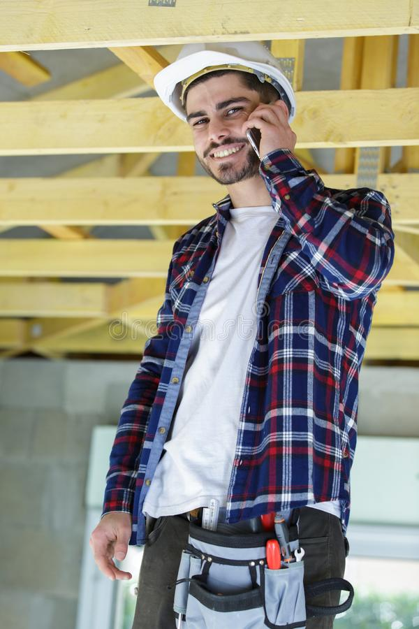 Uśmiechnięty męski budowniczy opowiada na telefonie zdjęcia royalty free
