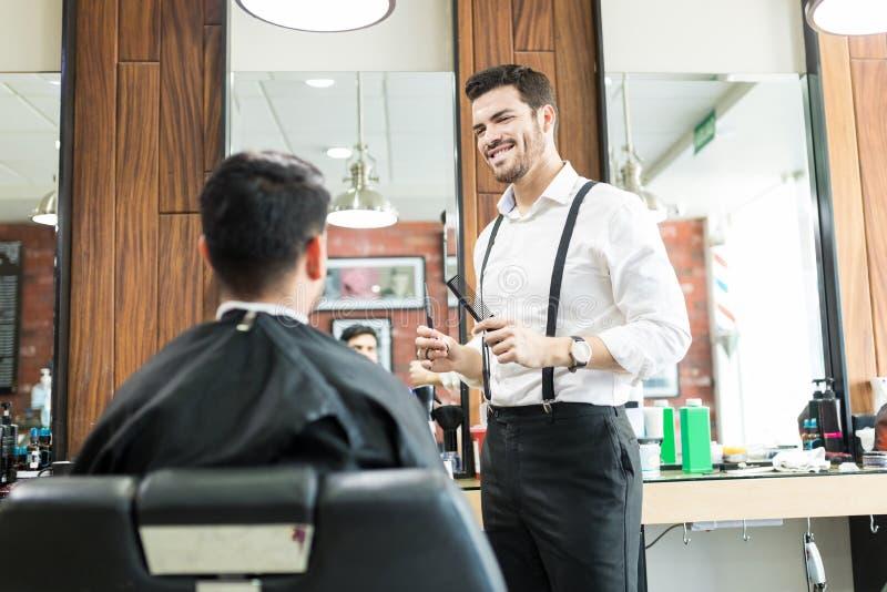 Uśmiechnięty Męski Hairstylist Patrzeje klienta W fryzjera męskiego sklepie obraz royalty free