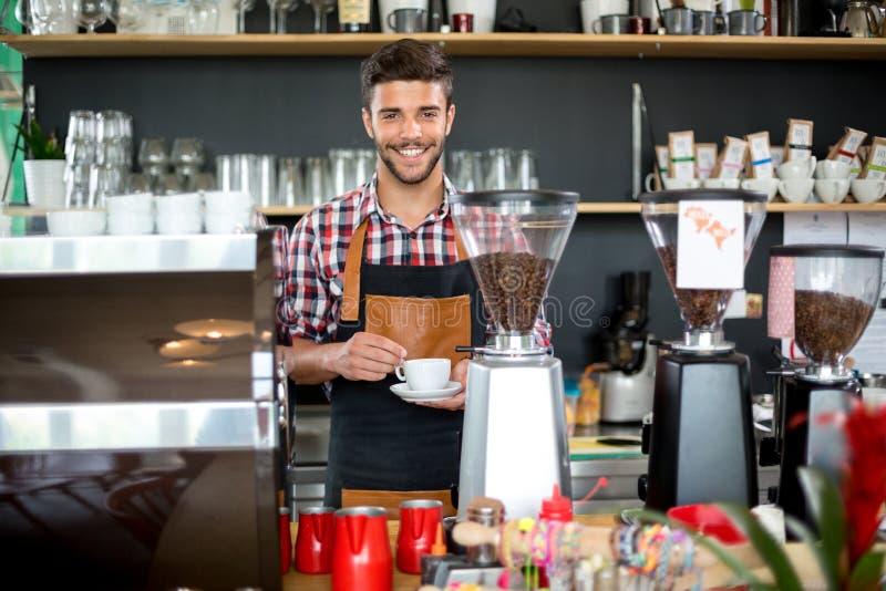Uśmiechnięty męski kelner trzyma filiżankę kawy obraz stock