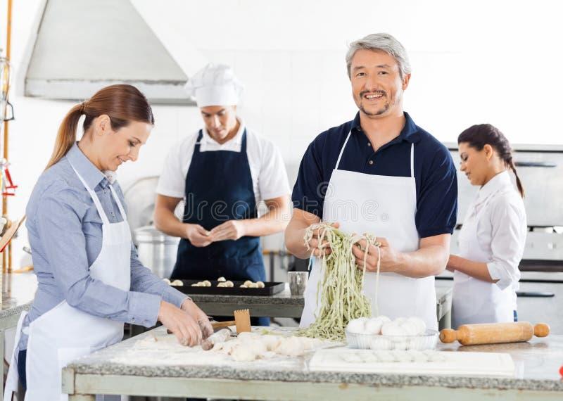 Uśmiechnięty Męski szef kuchni Z kolegami Przygotowywa makaron zdjęcia stock