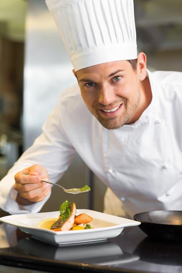 Uśmiechnięty męski szefa kuchni garnirowania jedzenie w kuchni obraz royalty free