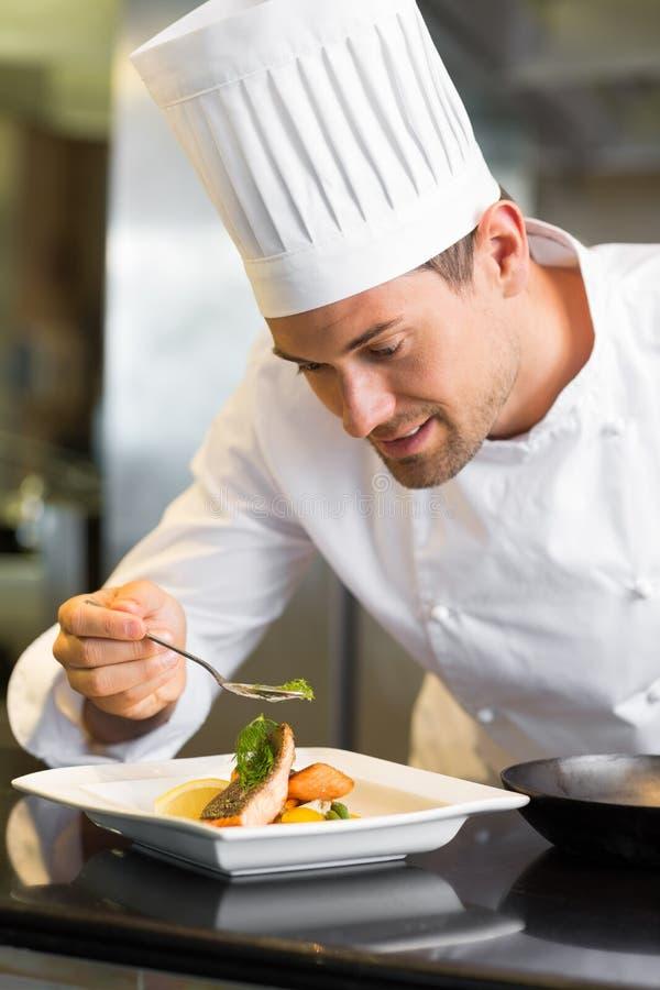 Uśmiechnięty męski szefa kuchni garnirowania jedzenie w kuchni fotografia royalty free