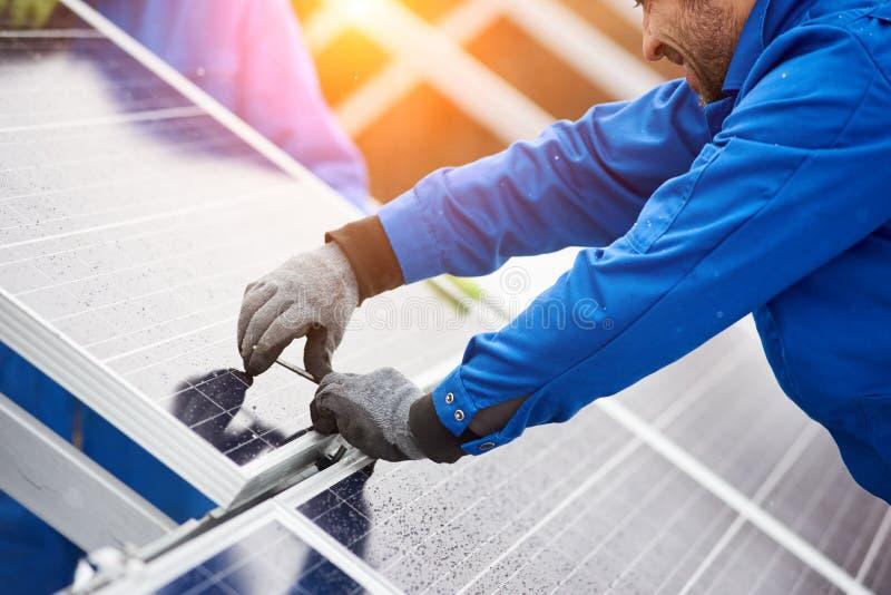 Uśmiechnięty męski technik instaluje photovoltaic błękitnych słonecznych moduły z śrubą w błękitnym kostiumu obraz stock