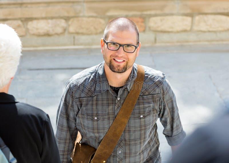 Uśmiechnięty Męski uczeń Z torby pozycją Na kampusie zdjęcia royalty free