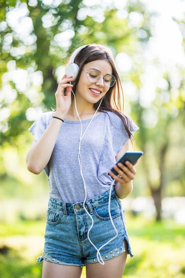 Uśmiechnięty młoda dziewczyna ucznia mienia telefon komórkowy, chodzący przy parkiem, słucha muzyka z słuchawkami fotografia stock