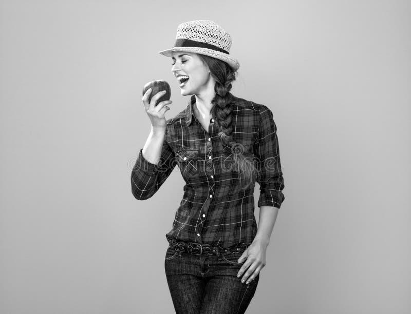 Uśmiechnięty młoda kobieta hodowca je jabłka na żółtym tle zdjęcie royalty free