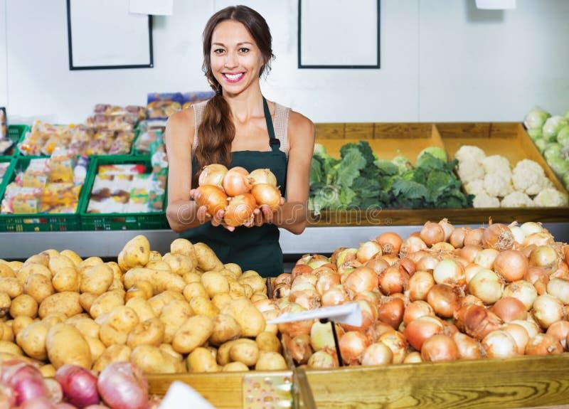 Uśmiechnięty młoda kobieta sprzedawca pokazuje żółte cebule zdjęcie royalty free