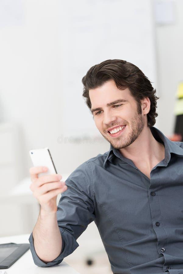 Uśmiechnięty młodego człowieka czytać sms na jego wiszącej ozdobie zdjęcia stock