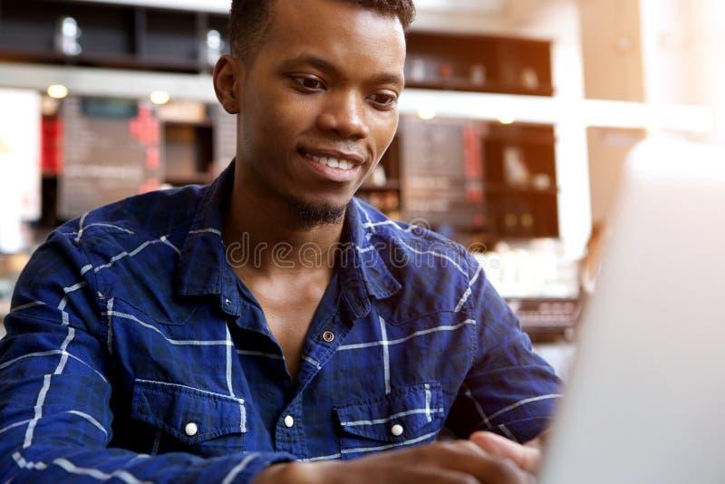 Uśmiechnięty młodego człowieka obsiadanie w cukiernianym działaniu na laptopie zdjęcia royalty free