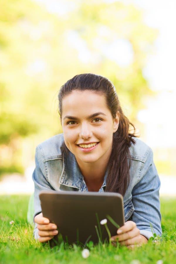 Uśmiechnięty młodej dziewczyny pastylki komputer osobisty kłama na trawie obrazy royalty free