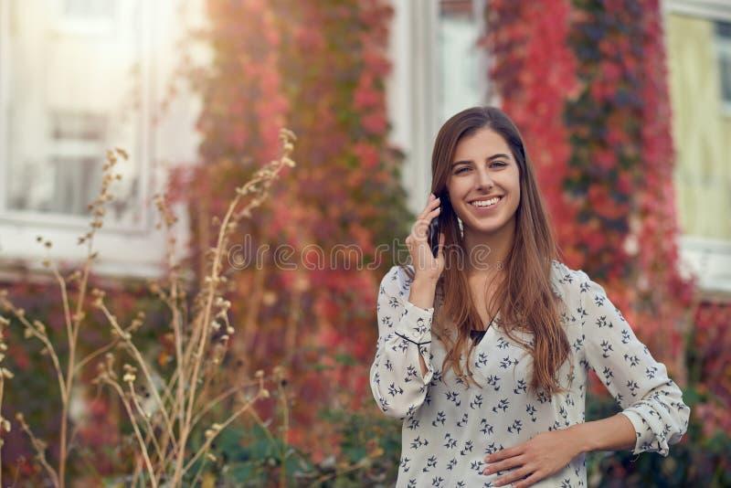Uśmiechnięty młodej kobiety gawędzenie na wiszącej ozdobie obrazy royalty free