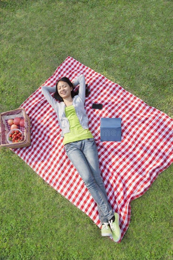 Uśmiechnięty młodej kobiety lying on the beach na ona z rękami za ona kierownicza na koc i relaksować w parku z powrotem obraz stock