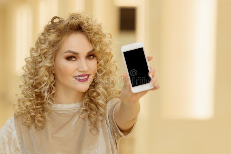 Uśmiechnięty młodej kobiety mienia telefon komórkowy w centrum handlowym fotografia stock