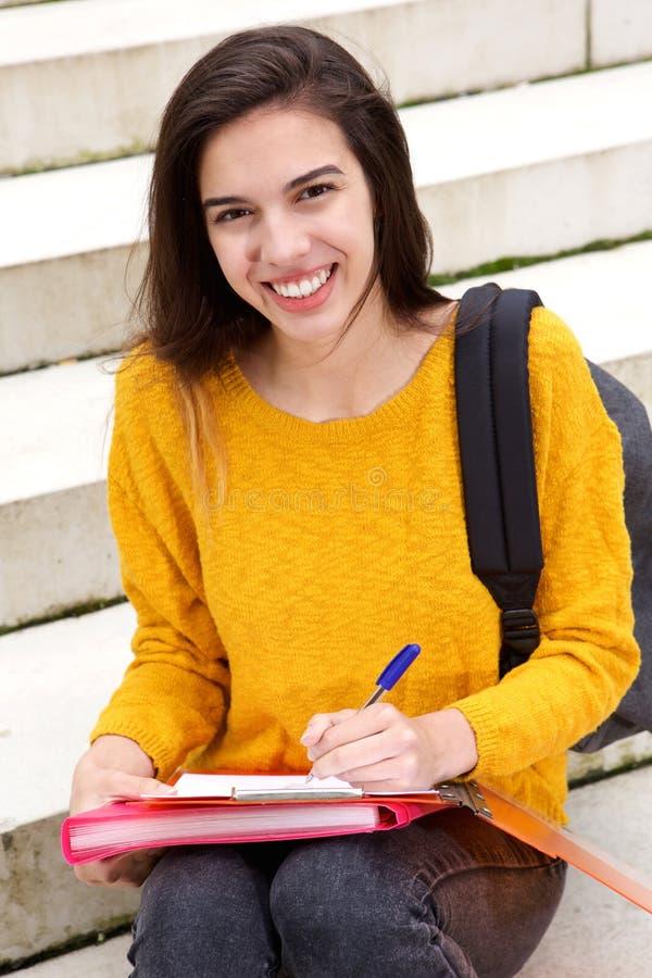 Uśmiechnięty młodej kobiety obsiadanie na krokach przy uniwersytetem zdjęcia royalty free