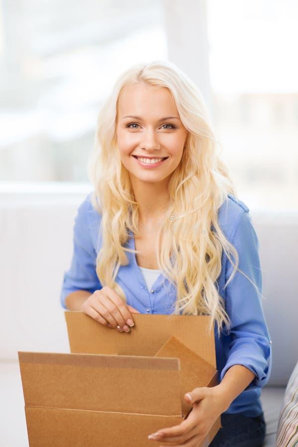 Uśmiechnięty młodej kobiety otwarcia karton fotografia stock