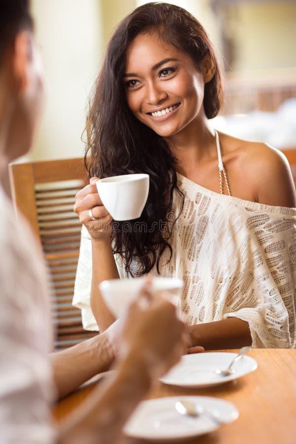 Uśmiechnięty młodej kobiety pić kawowy patrzejący jej chłopaka zdjęcia stock