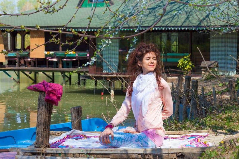 Uśmiechnięty młodej kobiety praktyki joga wiosny plenerowy letni dzień jeziornym pełnym ciało strzałem fotografia royalty free