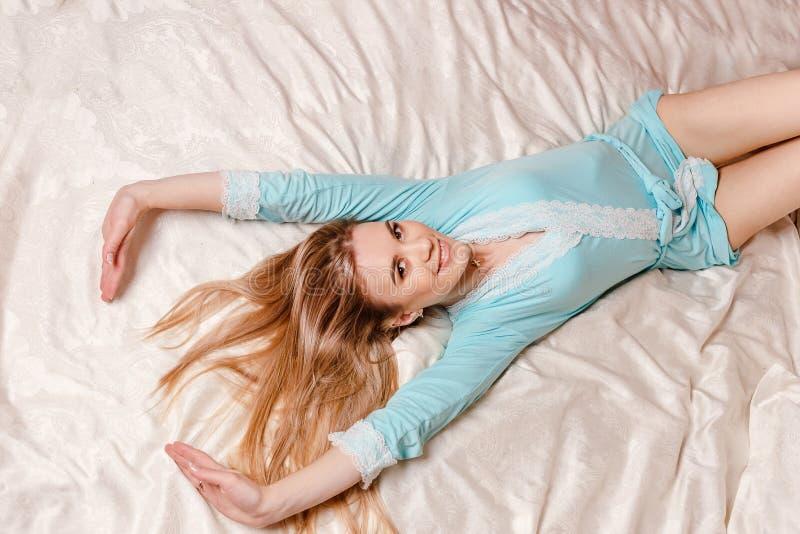 Uśmiechnięty młodej kobiety rozciąganie w łóżku zdjęcia royalty free