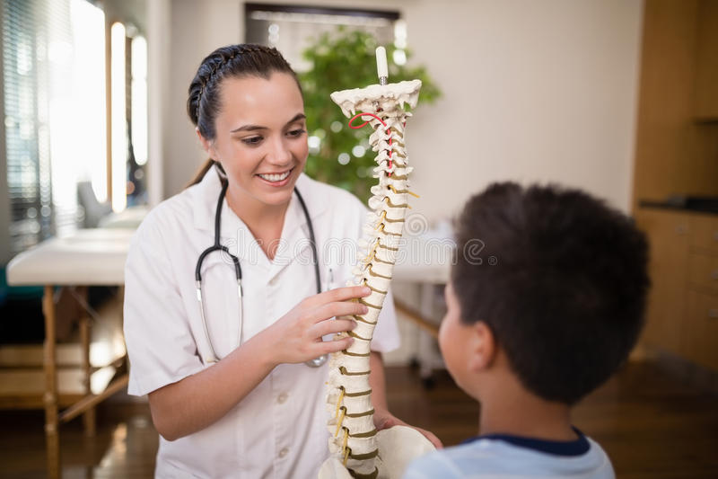 Uśmiechnięty młody żeński terapeuta wyjaśnia chłopiec o kręgosłupie zdjęcie stock