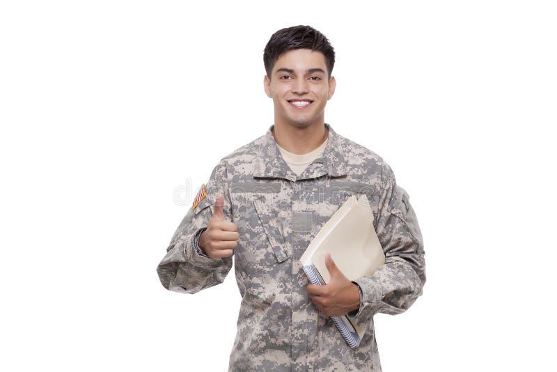 Uśmiechnięty młody żołnierz gestykuluje aprobaty z dokumentami zdjęcia stock