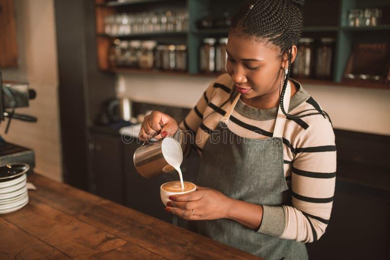 Uśmiechnięty młody Afrykański barista robi świeżej filiżance cappuccino obraz stock