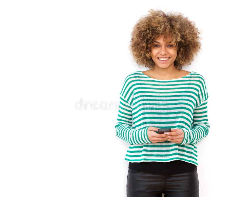 Uśmiechnięty młody amerykanin afrykańskiego pochodzenia kobiety mienia telefon komórkowy przeciw białemu tłu zdjęcia stock