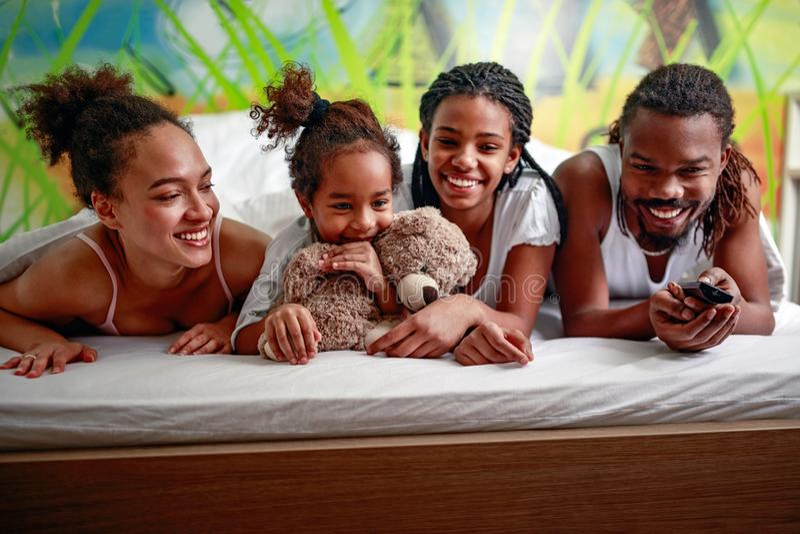 Uśmiechnięty młody amerykanin afrykańskiego pochodzenia rodzinny ogląda TV wpólnie obraz royalty free