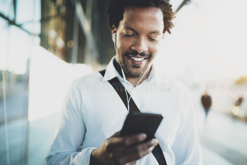 Uśmiechnięty młody amerykanina afrykańskiego pochodzenia mężczyzna w hełmofonu odprowadzeniu przy pogodnym miastem i cieszyć się  zdjęcie royalty free