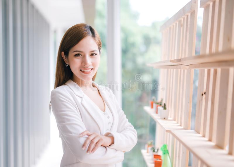 Uśmiechnięty młody Azjatycki bizneswoman z rękami krzyżować zdjęcie stock