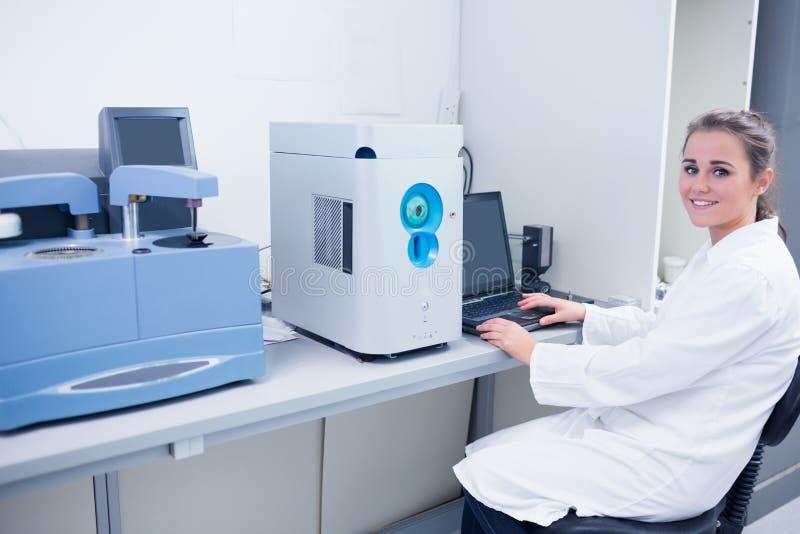 Uśmiechnięty młody biochemik używa laptop przy jej biurkiem obrazy royalty free