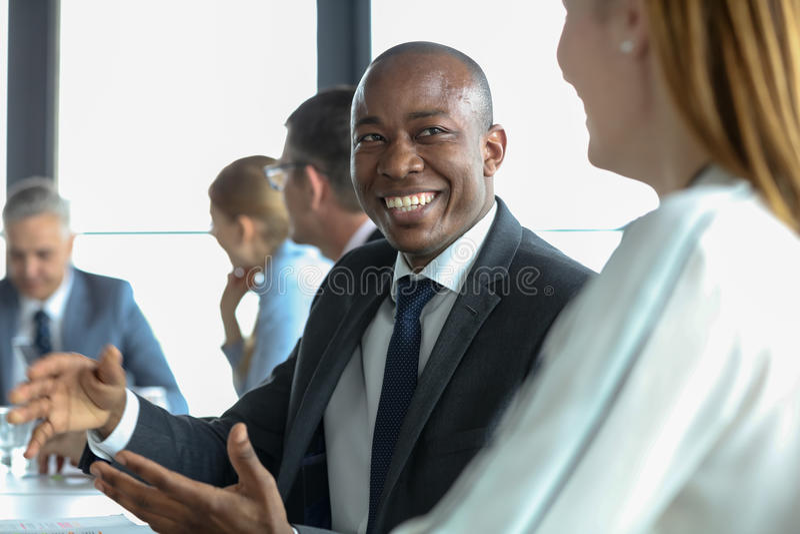 Uśmiechnięty młody biznesmen dyskutuje z żeńskim kolegą w deskowym pokoju zdjęcia stock