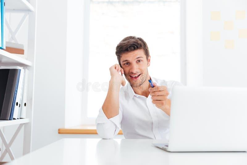 Uśmiechnięty młody biznesmen opowiada na telefonie komórkowym i wskazuje pióro zdjęcia stock