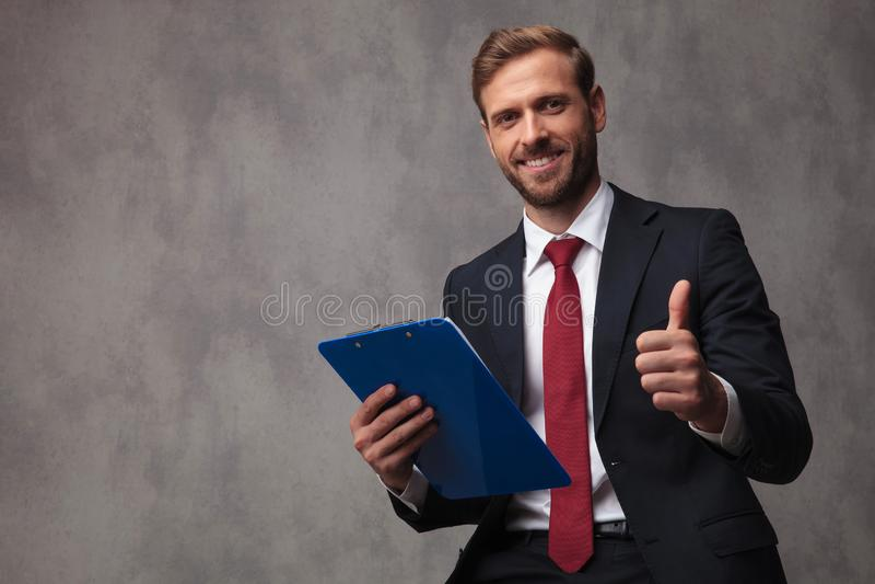 Uśmiechnięty młody biznesmen trzyma schowek robi ok znakowi obraz stock