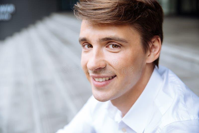 Uśmiechnięty młody biznesmen w białym koszulowym obsiadaniu outdoors obrazy stock