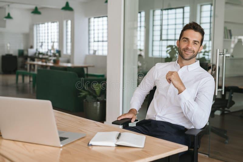 Uśmiechnięty młody biznesmena obsiadanie przy jego biurkiem w biurze fotografia stock