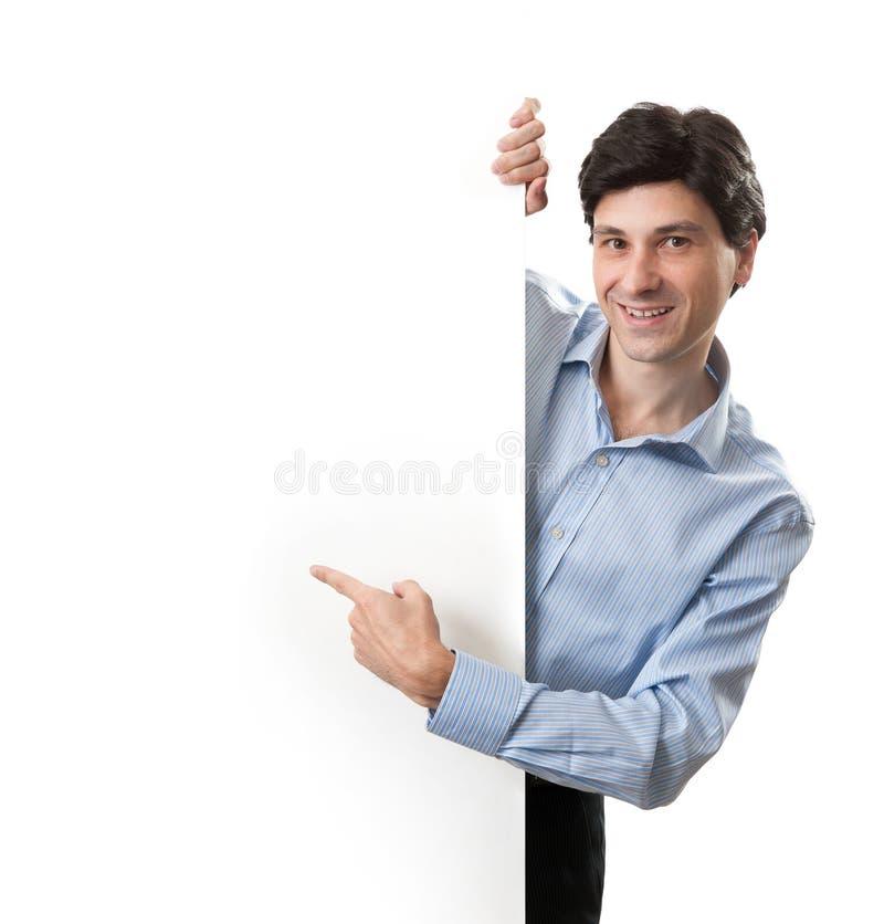 Uśmiechnięty młody biznesowy mężczyzna pokazuje pustego signboard obraz stock